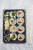 Sushi menu in black transportbox or bento box on gray background, top view, close up Stock Images