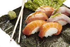 Sushi menu with six nigiri. Lying on seaweed with chop sticks and wasabi Stock Photo