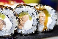 Sushi messi: rotolo di sushi con il rotolo di sushi e del salmone con l'anguilla affumicata, fuoco selettivo fotografia stock