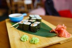 Sushi mit einer Gurke auf einem hölzernen Brett Stockfotografie