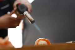 Sushi mit roher brennender Lachsflamme Lizenzfreie Stockfotos