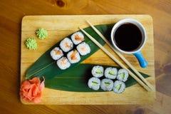 Sushi mit Soße auf einem hölzernen Brett Stockfoto