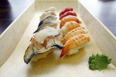 Sushi Mix. Japanese Food - a variety of traditional raw sushi and wasabi served on a wooden tray Royalty Free Stock Images