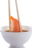 Sushi nigiri in chopsticks dipped in soy sauce isolated Royalty Free Stock Photos