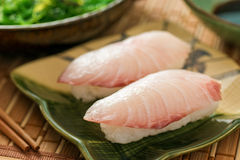 Sushi Nigiri. A delicious white fish nigiri-zushi with rice, wasabi paste, and japanese soy served with seaweed salad Stock Photo
