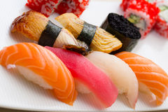 Sushi nigiri made dish with gunkan and roll. Sushi nigiri made dish with gunkan with black tobiko and roll with red tobiko on white plate Royalty Free Stock Images