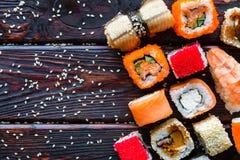 Sushi, nigiri y rollos de diversos gustos en un fondo negro Imagen de archivo