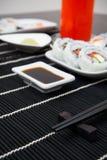 Sushi och pinnar på svart mattt Royaltyfria Foton