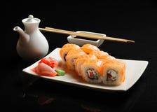 Sushi och rullar på en fyrkantig platta med wasabi, soya och pinnar på en svart bakgrund Royaltyfri Fotografi