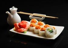 Sushi och rullar på en fyrkantig platta med wasabi, soya och pinnar på en svart bakgrund Royaltyfri Foto
