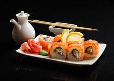 Sushi och rullar på en fyrkantig platta med wasabi, soya och pinnar på en svart bakgrund Royaltyfri Bild