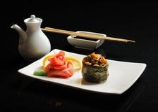 Sushi och rullar på en fyrkantig platta med wasabi, soya och pinnar på en svart bakgrund Arkivbilder