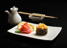 Sushi och rullar på en fyrkantig platta med wasabi, soya och pinnar på en svart bakgrund Arkivfoton