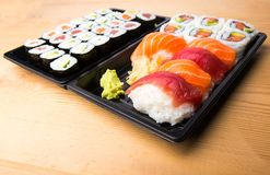 Sushi och sashimien rullar på en trätabell Ny gjord sushiuppsättning med laxen, räkor, wasabi och ingefäran Traditionell japansk  Arkivfoton