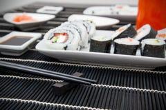 Sushi och soya på matt bambu Fotografering för Bildbyråer
