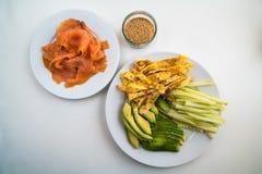 Sushi - olika ingredienser på plattor ordnar till och förberett Royaltyfri Bild