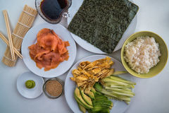 Sushi - olika ingredienser på plattor ordnar till och förberett Royaltyfri Foto