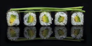 Sushi op een glanzende zwarte oppervlakte worden geschikt die heerlijk kijken die Stock Foto