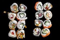 Sushi op een Zwarte Achtergrond Sushi op een lijst worden geplaatst die Hoogste mening Aziatisch of Japans voedsel stock afbeelding