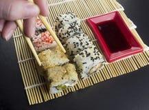 Sushi op een zwarte achtergrond, stokken, handsushi royalty-vrije stock foto's