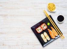Sushi op Zwarte Plaat met Sojasaus en Gember op Exemplaarruimte Royalty-vrije Stock Afbeeldingen