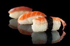 Sushi op zwarte worden geplaatst die Stock Foto
