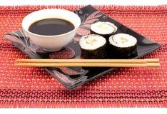 Sushi på en svart platta på ett rött mattt med pinnar Arkivbild