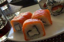 Sushi på en vit platta med rött vin Arkivbilder