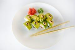 Sushi, petit pain et baguette japonais de fruits de mer d'un plat blanc Photographie stock libre de droits