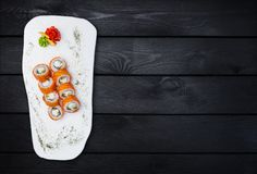 Sushi. Philadelphia roll with a cucumber, avocado, some cream cheese and salmon. Top view. Black wooden background. Sushi. Philadelphia roll with a cucumber stock photos