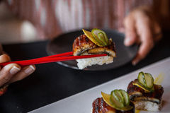 Sushi Picked Up by Red Chopsticks. Royalty Free Stock Image