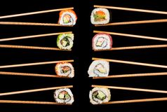 Sushi pieces in chopsticks Stock Photography