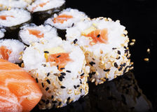 Sushi pieces over black reflecting plate Stock Photo