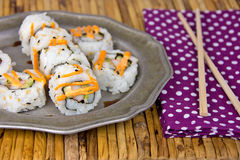Sushi pinwheels on pewter plate. Spicy sauce on sushi with chopsticks on polka dot napkin and bamboo place mat Royalty Free Stock Photography