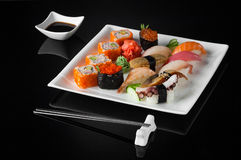Sushi in a plate on a black background Royalty Free Stock Images