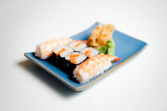 Sushi plate with hosomaki and nigiri. Blue sushi plate with hosomaki and nigiri selective focus on white background Stock Photography