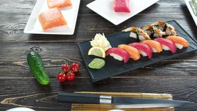 Sushi plate on wooden table. Nigiri, ginger and wasabi stock video