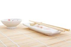 Sushi Plates And Chopsticks On Bamboo Mat Royalty Free Stock Photos