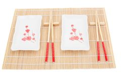 Sushi plates and chopsticks on bamboo mat Stock Images