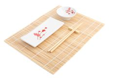 Sushi plates and chopsticks on bamboo mat Stock Image