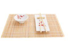 Sushi plates and chopsticks on bamboo mat Royalty Free Stock Photo