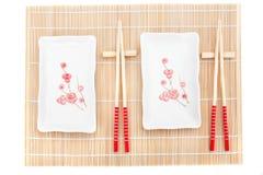 Sushi plates and chopsticks on bamboo mat Stock Photography