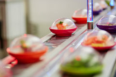 Sushi plates on rails in Japanese restaurant Stock Photography