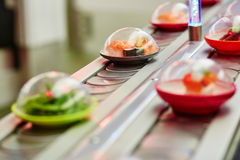 Sushi plates on rails in restaurant Stock Photo