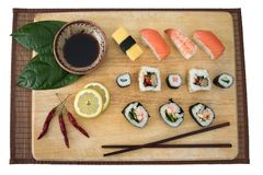 Sushi platter. Platter of sushi on a wooden board, comprising of several types of sushi, soy sauce, chopsticks etc Royalty Free Stock Photo