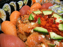 Sushi platter. Closeup of sushi platter with salmon, tuna, avocado, tempura, caviar, nigiri and maki rolls with sesame seeds Stock Images