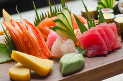 Sushi Platter. A colorful platter of sashimi sushi with tuna and crab sticks in foreground and cucumber decorations Stock Photography