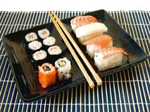 Sushi platter meal. Healthy Japanese meal of assorted sushi on a blue ceramic platter with wooden chopsticks and bamboo mat against a white background Stock Image