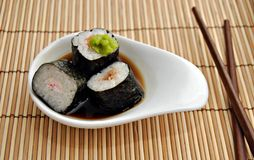 Sushi pot. Sushi appetizer served in a small dish with green sauce on top and sticks to the sides Stock Images