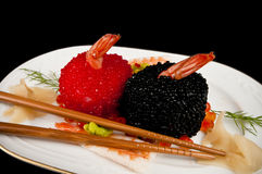 Sushi with prawns, red and black fish eggs. Norimaki sushi with prawns, covered in red and black fish eggs with salmon eggs garnish.  On a Japanese dish with Royalty Free Stock Image